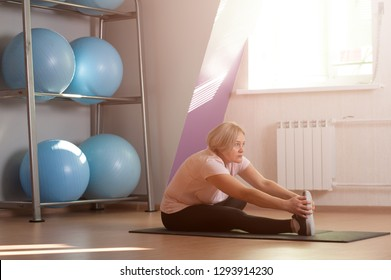 Pretty Middle aged woman does stretching after a workout. The concept of health and longevity