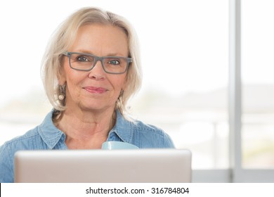 A pretty middle aged woman looks past her laptop computer