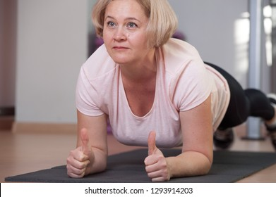 Pretty middle aged woman practicing plank pose at the gym. The concept of flexible ligaments and a healthy body in adulthood