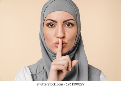 Pretty Middle eastern arabian muslim islamic young woman in grey hijab making silent gesture isolated over beige background. Top secret. relogion, Islam, confession, women`s rights concept