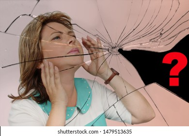 pretty middle-aged woman with facial expressions of fatigue raised her hands to her head against the background of broken glass with cracks, copy space, isolate