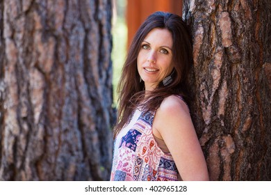 Pretty middle-aged woman leaning back against a tree