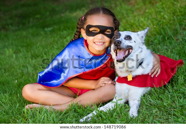 Pretty mixed race girl hugging her pet  with both dressed up in super hero costumes