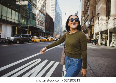Pretty mixed race woman calling yellow taxi cab in Manhattan, New York. Inspiring photo of stylish student girl in the big city.