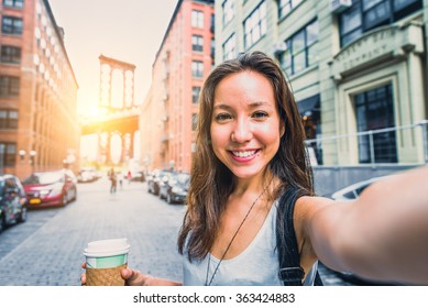 Pretty mixed race woman taking a selfie in New York, Brooklyn Bridge in the background - Beautiful girl walking on the streets of NY and photographing some landmarks
