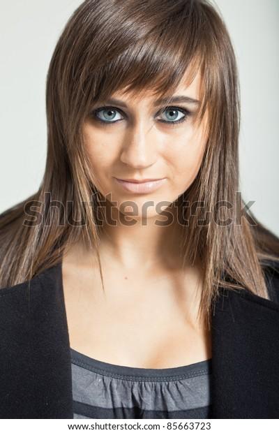 Pretty model in a black coat against white background