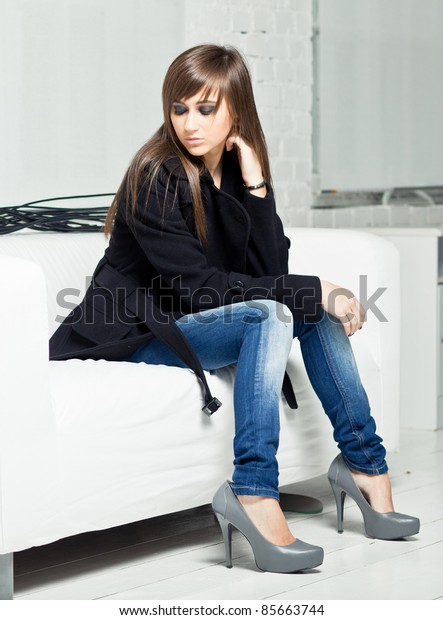 Pretty model in a black coat against white background