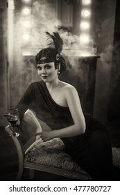 Pretty model. Flapper girl with wineglass. Old photo in a retro style. Smoky eyes, hairstyle cold wave. Creative colors. Hair ornament with ostrich feathers, lace bandage.
