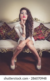 Pretty model girl wearing white dress sitting on victorian sofa posing for camera looking into camera