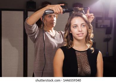 Ein hübsches Modell ist ein Haar, das von einer Stylistin in einem Schönheitssalon in einer Meisterklasse kurbelt wird. Konzept des professionellen Friseurstudiums