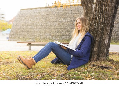 Pretty model sitting reclined tree and reading
