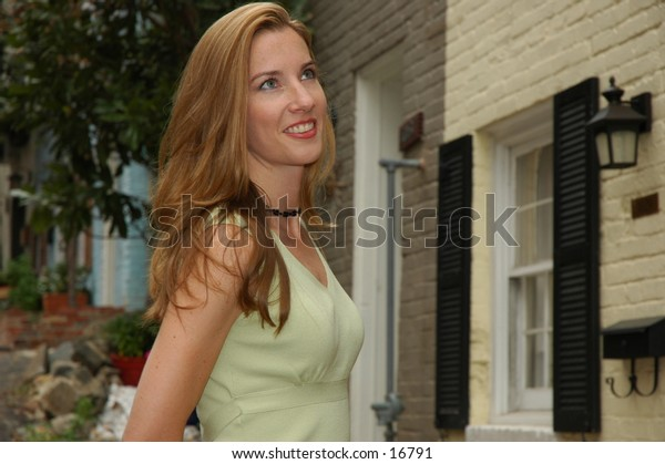 Pretty model smiling and looking away in front of house