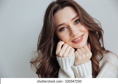 Pretty model in sweater in studio. looking at camera. isolated gray background