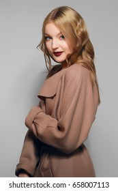 Pretty model in warm wool coat. Fresh healthy skin, natural make-up and red lips.