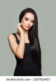 Pretty model woman with long straight hair and makeup wearing black dress posing against gray wall background
