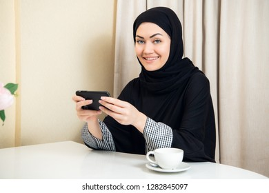 Pretty modern Arabic woman playing on smart phone at home
