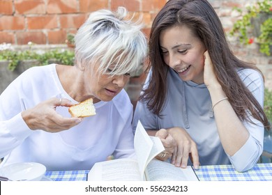 pretty mom and daughter reading a book while having breakfast outdoors