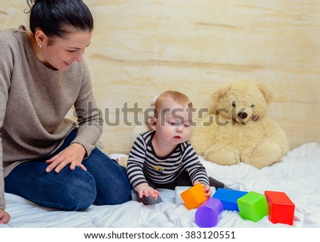 c4942e7c6 Pretty Mom with her Cute Baby Boy Playing Colored Plastic Toys at Home  Together.