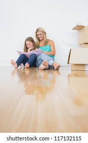 Pretty mother and daughter reading a book together on the floor near moving boxes