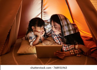 Pretty mother and daughter watching cartoons on digital tablet