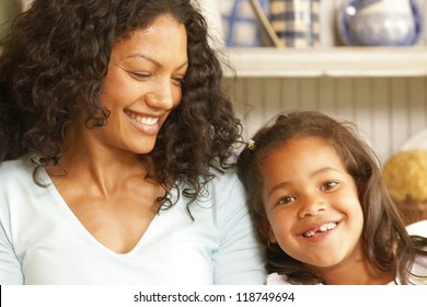 Pretty mother grins as her cute little girl smiles showing her missing teeth
