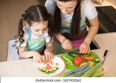 Pretty mother and her child making vegetable salad