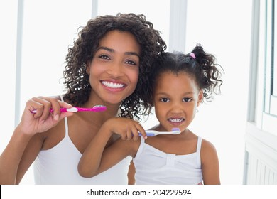 Pretty mother with her daughter brushing their teeth at home in the bathroom