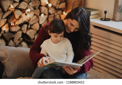 Pretty mother and her little daughter reading book in the evening at home with cozy and christmas decoration. Beautiful woman and cute little girl have literature. Family, hygge and people concept