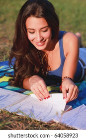 Pretty multicultural college teenager studying outdoors in a university campus.