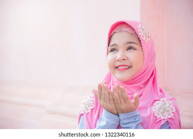 Pretty muslim girl is raising hands ask for blessing from God.