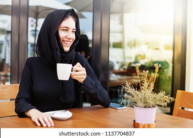 Pretty muslim woman having coffee in a cafe