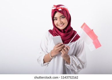 pretty muslim woman using mobile phone. indonesian independence day celebration