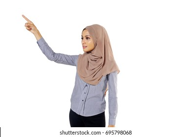 A pretty Muslim woman wearing hijab use her hands sign towards show an empty space.