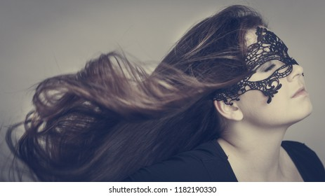 Pretty mysterious woman wearing black eye lace mask having tousled windblown long brown hair.