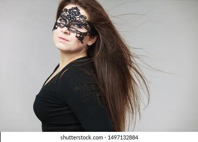 Pretty mysterious woman wearing black eye lace mask having tousled windblown long brown hair.