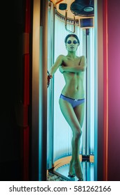 pretty naked woman or cute girl with sexy healthy body standing in solarium spa salon in pants and sunglasses, has beautiful belly and chest