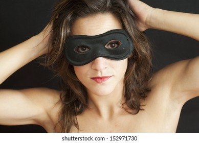 Pretty naked woman with mask over black background