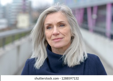 Pretty natural grey blond middle-aged woman with a lovely smile looking into the lens as she stands on an outdoor pedestrian walkway in town