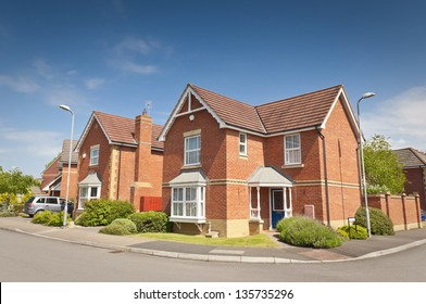Pretty newly built homes and gardens against a clear blue summers sky.