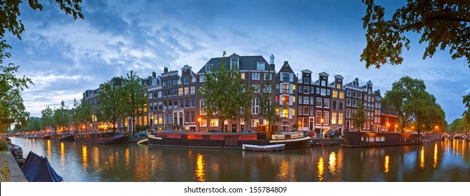 Pretty night time illuminations of dutch doll houses reflected in the tranquil canals of Amsterdam.