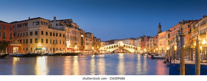 Pretty night time illuminations of the iconic Rialto Bridge (1591) and Venetian Villas over the grand canal in Venice. Stitched panoramic image.