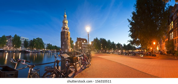 Pretty night time illuminations of the Montlebaanstoren Tower (1512) overlooking Oosterdok and the ubiquitous dutch bicycles in central Amsterdam.