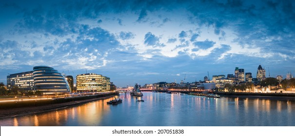 Pretty nighttime illuminations of the River Thames, many sights visible including London City Hall, HMS Belfast, Tower of London and the cities financial district.