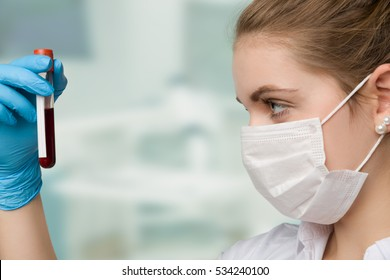 pretty nurse with face mask is holding a blood sample in a laboratory