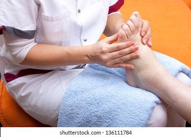 pretty  Nurse treats a patient's foot