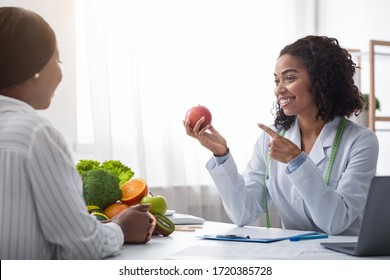 Pretty nutritionist black woman giving consultation to patient with healthy fruit and vegetable, nutrition and diet concept, copy space