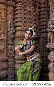 Pretty Odissi dancer striking pose against the backdrop of Mukteshvara Temple with sculptures in bhubaneswar, Odisha, India