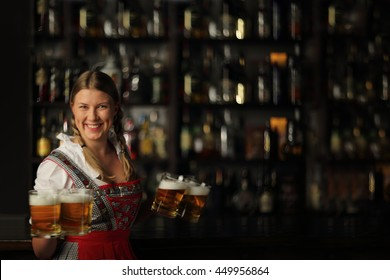 Pretty oktoberfest blonde woman holding beer mugs in bar