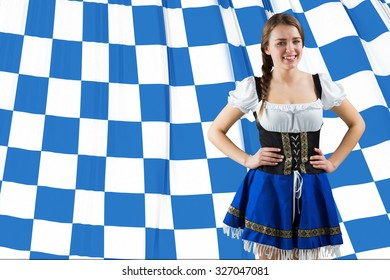 Pretty oktoberfest girl smiling at camera against blue and white flag