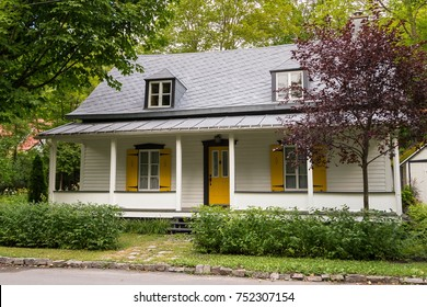 Pretty old white wooden country house with yellow shutters and metal tile roof in Ste. Petronille, Island of Orleans, Quebec, Cana